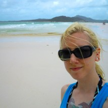Laura, wearing oversized black sunglasses and a blue tank gives a subdued smile. In the background is a shoreline made of white sand and blue-green water.