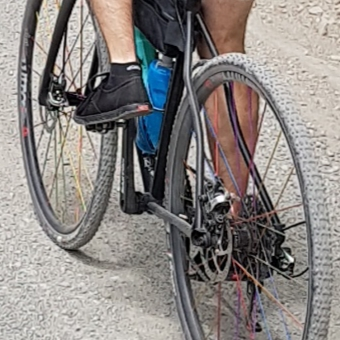 A slightly grainy, cropped close-up showing a cyclist pushing on pedals wearing black canvas shoes.