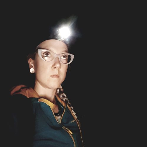 Woman wearing white cat eye glasses looks up. She is surrounded by darkness and has a lit headlamp on her head.