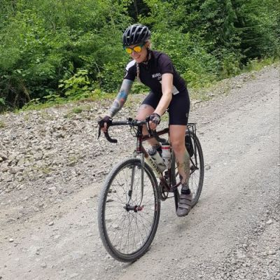 A white, tattooed female clad in black cycling gear rides over rocky terrain.