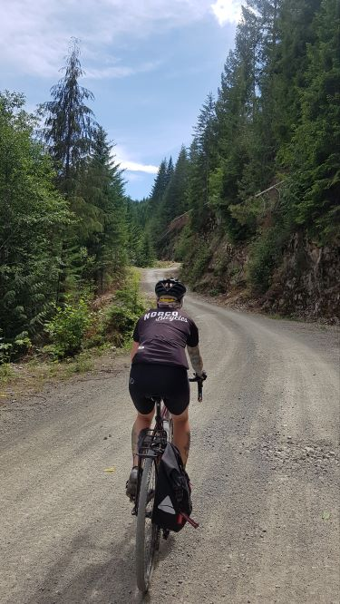 A rear view of a woman clad in black cycling gear riding down a winding gravel path surrounded by evergreen trees. A black pannier hangs off the right rear side of the bike.