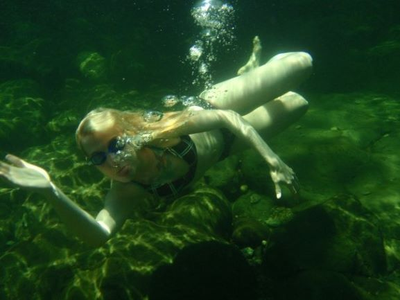 A pale blonde in a black bikini is waving underwater. She is wearing goggles and air bubbles are coming out of her nose.