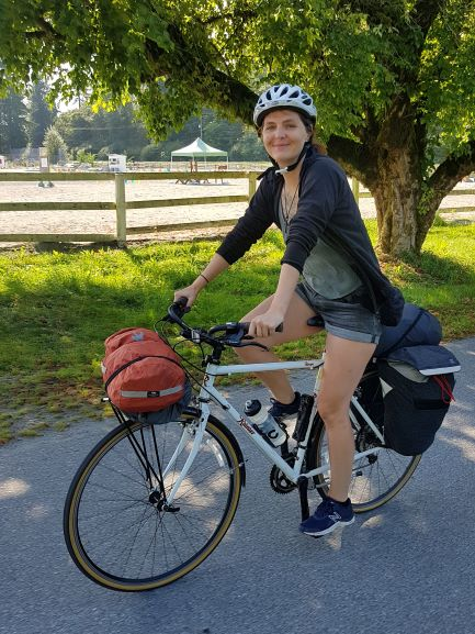 Woman rides a white bicycle with panniers mounted on the rear rack and additional gear strapped to the front rack. She is wearing a white helmet, black shirt with the sleeves rolled up, and shorts.