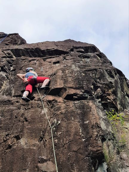 Laura stands hands-free on a rock face. A rope and two quickdraws are visible below her. She is wearing red capris, a blue tank top and a helmet. An orange chalk bag hangs off the back of her climbing harness.