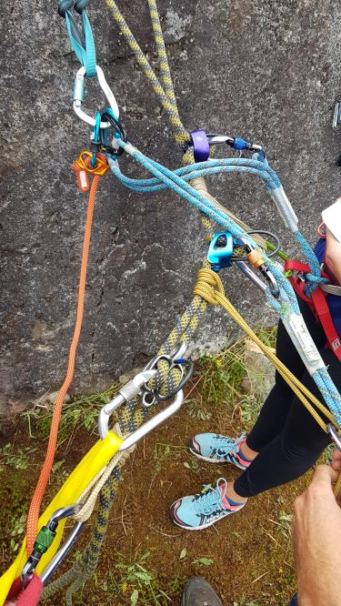 A seemingly tangled rappelling set-up. On the yellow and blue striped rope, three ATC devices are visible. Each ATC device is attached to someone's personal anchor system. Visible in the frame is someone's black legging clad legs and light blue sneakers.