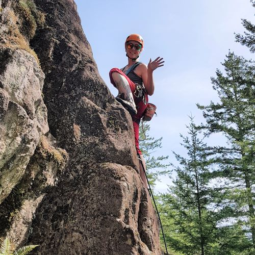 Laura waves from the middle of an eighty degree rock face. She is wearing an orange helmet, sunglasses, blue tank top, red capris and cllimbing shoes. An orange chalkbag hangs off the back of her harness. Trees are visible in the background.