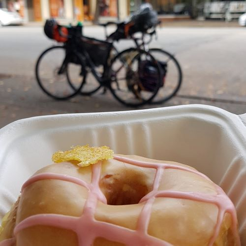 A donut with a tan coloured glaze base and a criss-cross of pink glaze sits in a paper clamshell food box while two out-of-focus bikes are visible in the background.