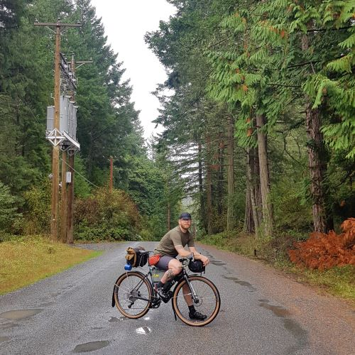 Ed poses on his bicycle on a wet road surrounded by trees. Ed is wearing a tiny cap, t-shirt, and shorts. Telephone poles can be seen on the left.