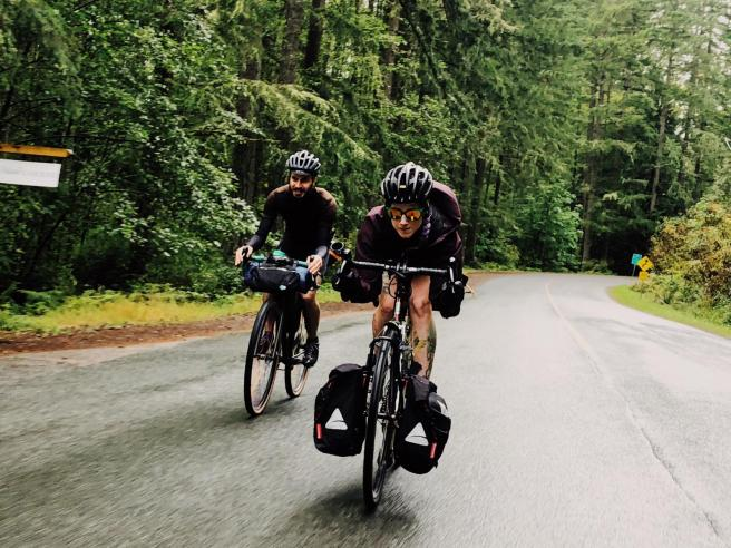 Laura gets aero on her bike while Yann follows behind. Laura is wearing a black helmet, sunglasses with reflective orange lenses and shorts. Her front panniers hang from the front rack. Yann, on the left, is dressed in all-black and is toting his gear in a handlebar bag. The road is wet and surrounded by trees.