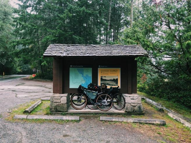 Two bicycles lean against a mini shelter. On the shelter, behind the bicycles is a map of Ruckle Provincial Park. Two concrete parking barriers lie in front of the shelter. Trees are visible in the background.