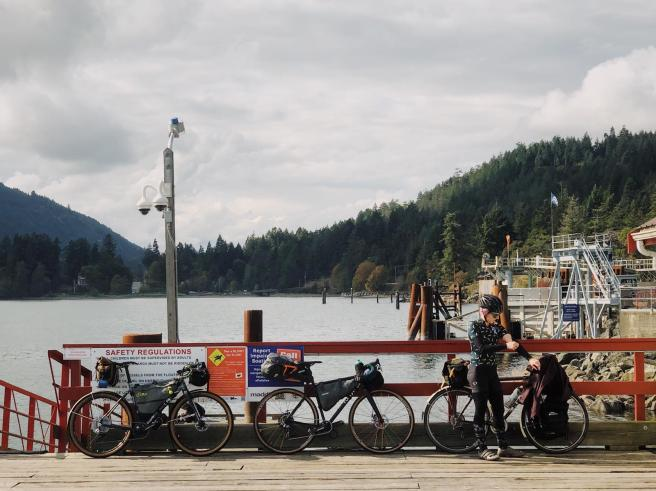 Three bikes lean against the railings of a dock. Laura stands on the right, in front of her bicycle, removing her arm warmer. The Fulford Harbour ferry terminal is visible in the background.
