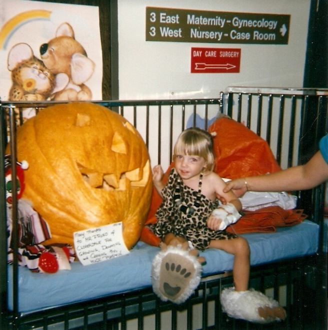 A three year-old Laura in a leopard print Halloween costume and fuzzy white bear claw slippers is seated next to a giant jack-o-lantern. Her left arm appears to be wrapped in a half-cast, which is actually an IV port. The arm of an adult is grabbing her upper arm.