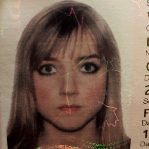 A passport photo of a young Laura (circa 2008). She has long dirty blonde hair which is cropped out of the photo, and bangs. She looks straight ahead at the camera, expressionless. She is wearing heavy black eye make up and excessive blush.