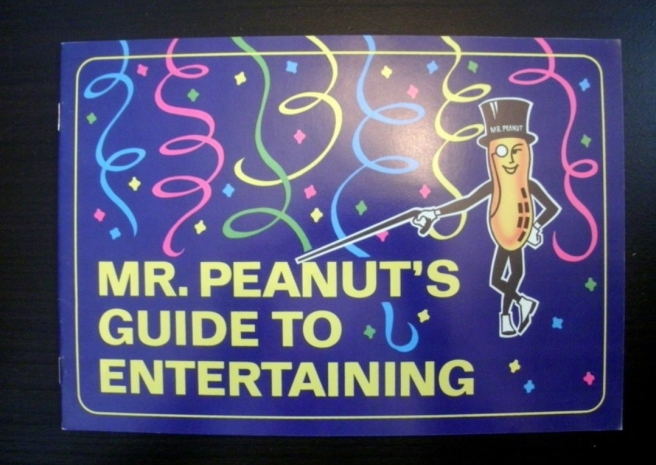 "Cover of a book titled ""Mr. Peanut's Guide to Entertaining"". The cover features streamers, confetti, and the Mr. Peanut character aiming his cane at the book title."