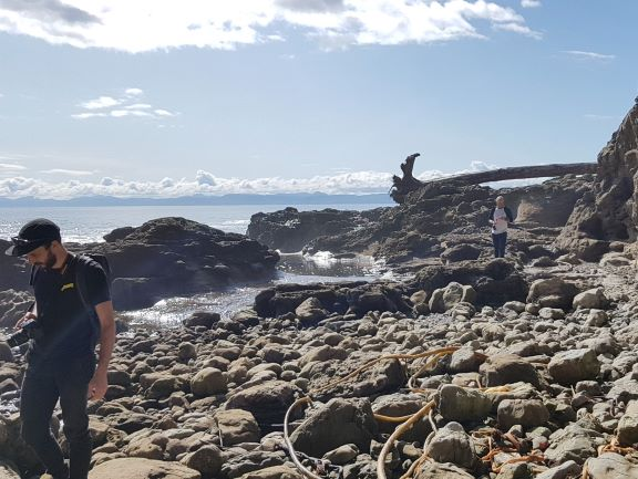 Yann, a bearded man dressed in a black cap, t-shirt and pants appears on the very left of the photo while Ed, dressed in a white baseball shirt and jeans follows behind. The bulk of the photo features large rocks on the beach.