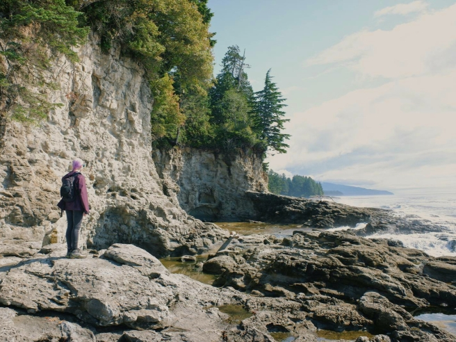 Laura stands on the rocky shore of Botanical Beach with her back to the camera. She is wearing a wine coloured rain jacket, skinny black jeans and a small black backpack. Her hair is lilac. Trees line the rocky cliffs above.