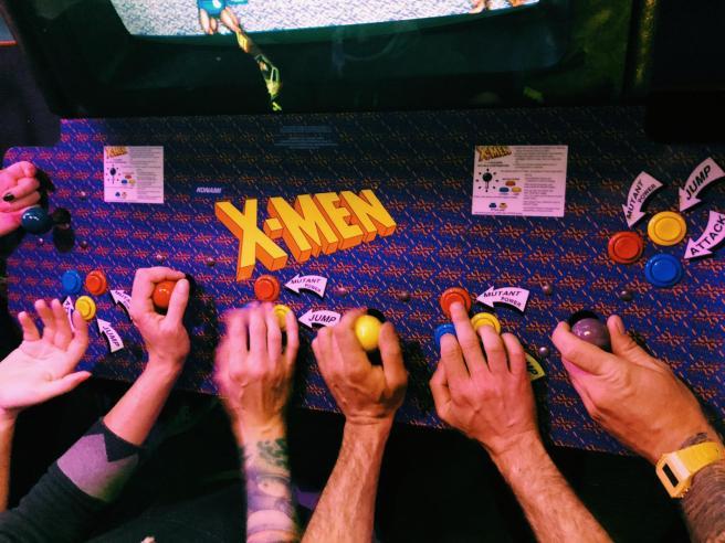 Seven hands are shown handling an X-Men arcade machine.