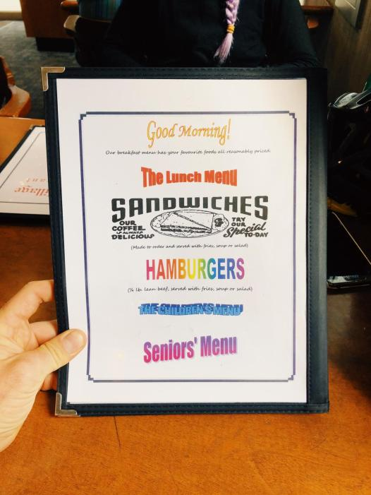 The back of a diner menu where the items have been typed out using Word Art. The menu reads: Good Morning! (followed by tiny text that I cannot read either) The Lunch Menu, Sandwiches, (more tiny text), Hamburgers, (tiny text again), The Children's Menu, and Seniors' Menu.