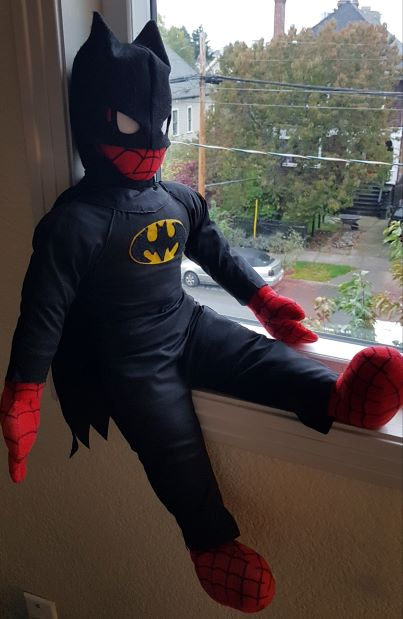 A Spiderman plushie dressed in a homemade Batman costume lounges on a windowsill.