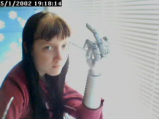 A tiny low-quality webcam photo featuring Laura with bangs and black hair. Her bangs have brassy blonde streaks in them. Her left arm appears to be a silvery arm from a mannequin.