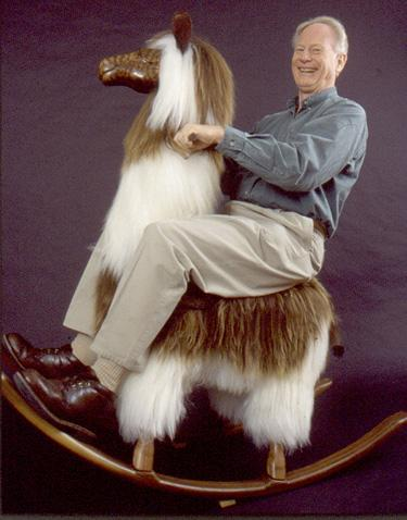 A random old white man with a big grin sits on a large rocking llama.