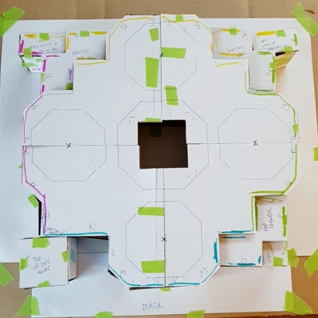 Birds eye view of the cardboard structure. The border of each side is colour coded, and in the middle there is a void. Green tape can be seen holding the structure together.