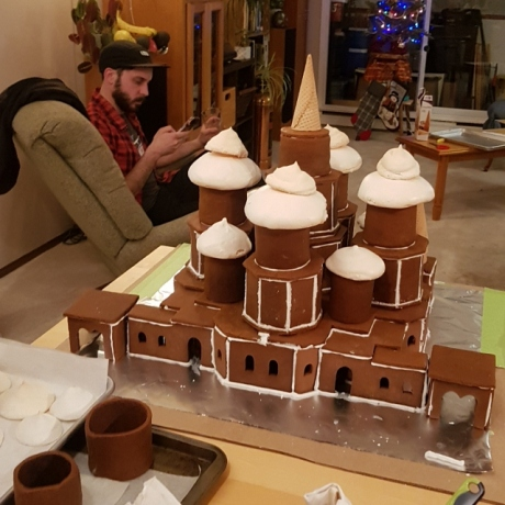 Gingerbread house pre-decoration. An inverted waffle cone can be seen on the top. To the left of the structure, is an out-of-focus Yann staring at his phone.