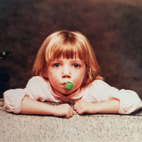 Laura at age two stares straight into the camera. In her mouth is a green plastic pipe from a Mr. Potato Head Toy.