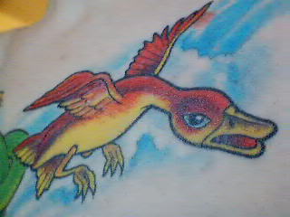 Close-up of a tattoo of a red and orange goose.