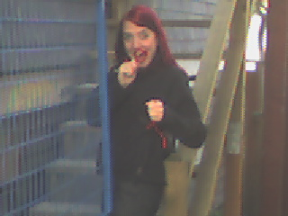 A low quality photo of me from circa 2006. My hair is red, and I'm dressed in black. In my hands are red strands of something (they were pipe cleaners, but the quality of the photo is so poor that even those with 20/20 vision wouldn't be able to tell).