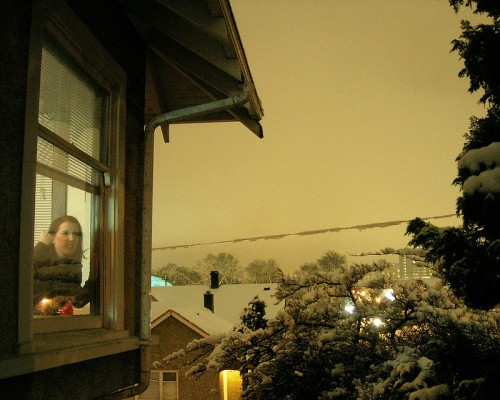 A 23-year-old Laura stands behind a window, shaking her fist at the winterscape.