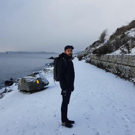 Yann, dressed in all-black and wearing a backpack, grimaces at the camera. The path by the beach is blanketed in snow.