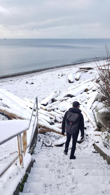Yann, with his back turned to the camera, descends snowy steps leading to a snow-covered beach.