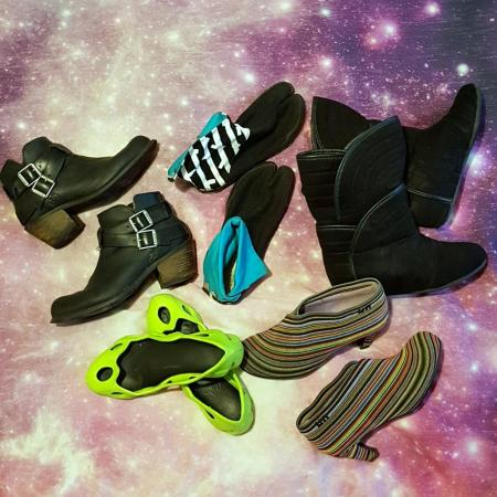 An assortment of footwear laid out on a galaxy print bedspread. They include, black leather ankle height boots with buckles and a chunky heel, lime green foam flats that look like Crocs from another planet, rainbow stripes wrapped around ankle height boots with low heels, and black boots that resemble Uggs, if Lady Gaga had redesigned the Ugg boots, and black and white tabi shoes with turquoise liners..