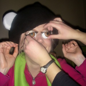 An extra set of hands adjusts fake eyes made from ping pong ball halves and false lashes. The fake eyes are attached to Laura, who is also wearing a mascot's headwear.