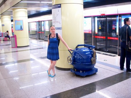 Laura in a blue summer dress with a shirred top leans one hand on the handle of a spherical blue device that resembles a safe. She is in a mostly empty Beijing subway station.