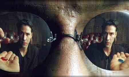 A still from The Matrix. A close-up of Morpheus' mirror sunglasses shows Keanu's reflection as he reaches for the red pill from the palm of one hand. In the other hand is the blue pill.