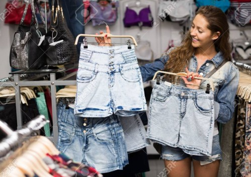 A stock photo image of a young white woman in a denim jacket and shorts holding up denim shorts on hangers. She appears to be in a clothing store.