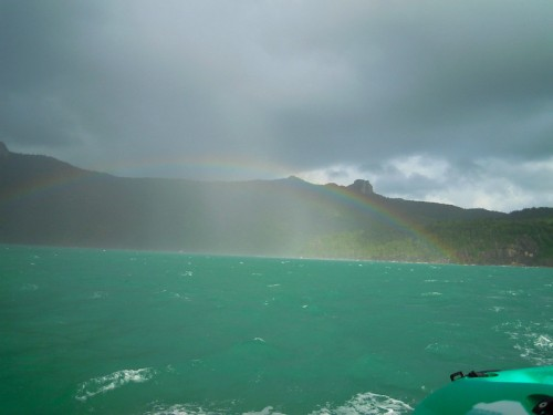 A low full arc of rainbow from the green-blue sea. Heavy clouds are visible above.