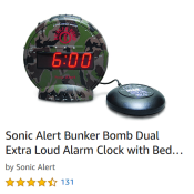A circular digital alarm clock with camo pattern is shown with a Smartie shaped device meant to be inserted under the pillow to shake the person awake. The text reads