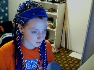 Me at 18 staring at the computer monitor. My hair has been wrapped in blue and white yarn and pulled out of my face with a blue bandana. I am wearing an orange t-shirt with the tiger logo from vintage Prowler trailers. In the background a white bookshelf can be seen and leaning against the bookshelf are two pool cues.