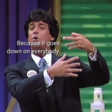 A tanned suit wearing man with a dark bouffant making wiggling motions with his fingers. The caption over his face says