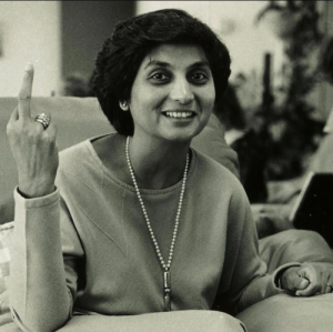 A black and white photo of a smiling lady with short dark hair flipping off the camera.