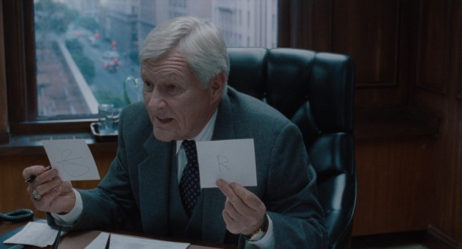 An old man (the late actor Orson Bean) holds up two flash cards. In his right hand, a symbol has been drawn and in his left, the letter