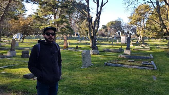 Yann, dressed in black and wearing sunglasses, stands in front of multiple burial plots.