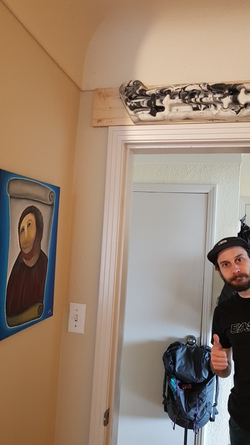 Yann stands in the doorway giving a thumbs up. A black and white marbled climbing hangboard has been mounted on a piece of plywood above the door. The painting on the wall on the left is a replica of Ecce Homo aka Fresco Jesus.