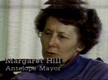 An older white woman with short curly dark hair looks away from the camera. Text on the bottom left reads: Margaret Hill Antelope Mayor.