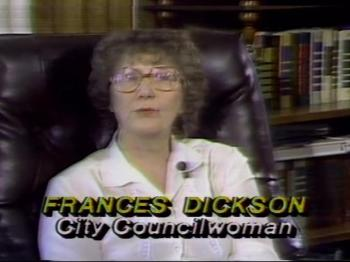 A short curly haired woman wearing a white blouse is seated in a large leather chair. The text on the bottom reads: Frances Dickson City Councilwoman.