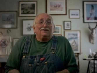 An obese bald old man with a white moustache and aviator glasses looks to the left. He is wearing a dark green t-shirt, blue coveralls. The wall behind him is covered in framed photos. On the right is the head of what appears to be an antelope. On the left is a white t-shirt, and above that, two horseshoes.