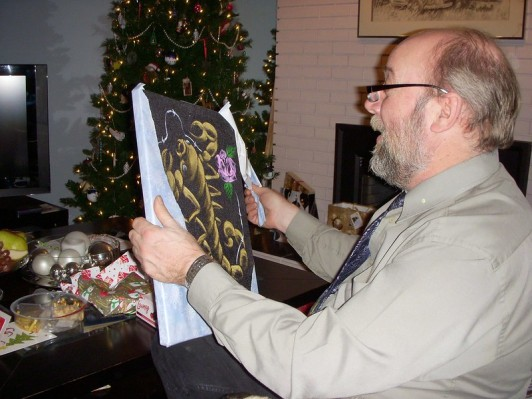 A graying, balding Boomer holds up a velvet painting featuring a gold scorpion, pink roses, and barbwire. A decorated Christmas tree is visible in the background.